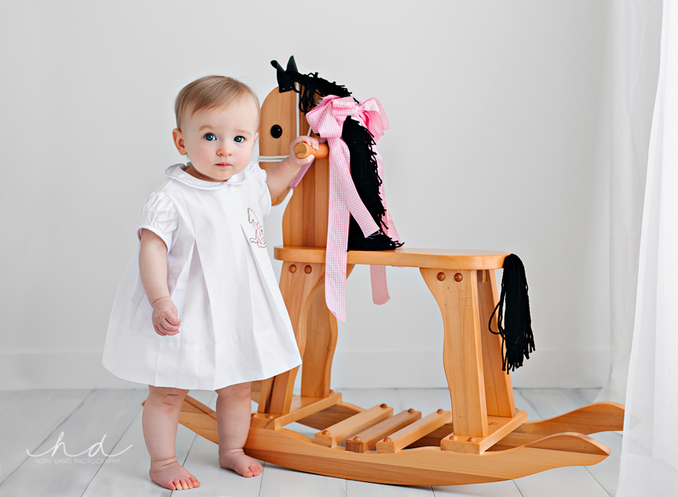 one year old baby girl with wooden horse