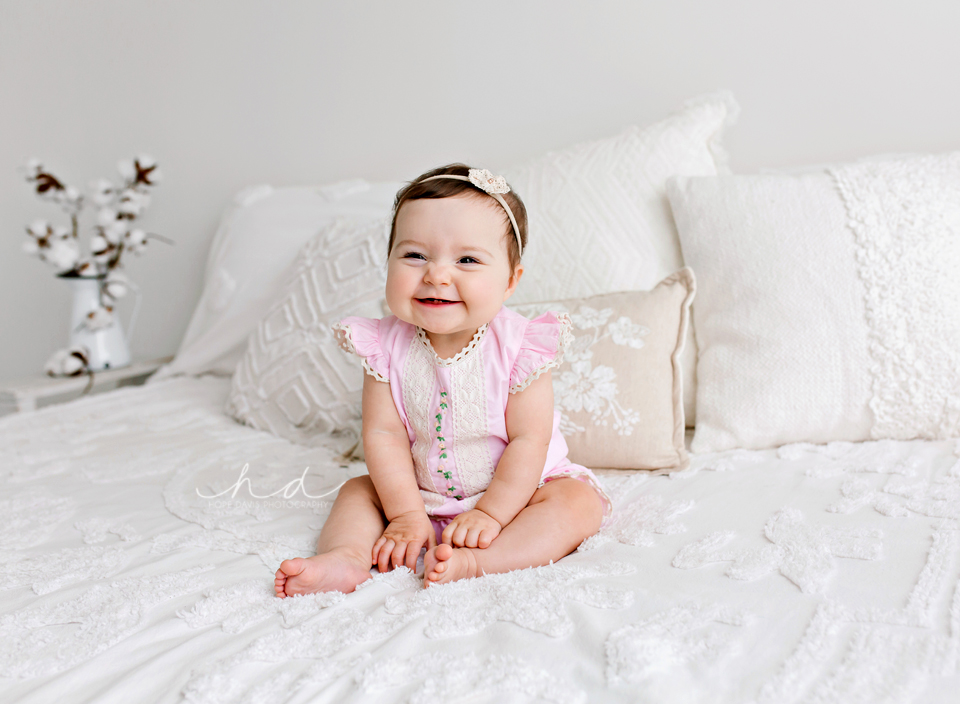 smiling 6 month old baby sitting on bed