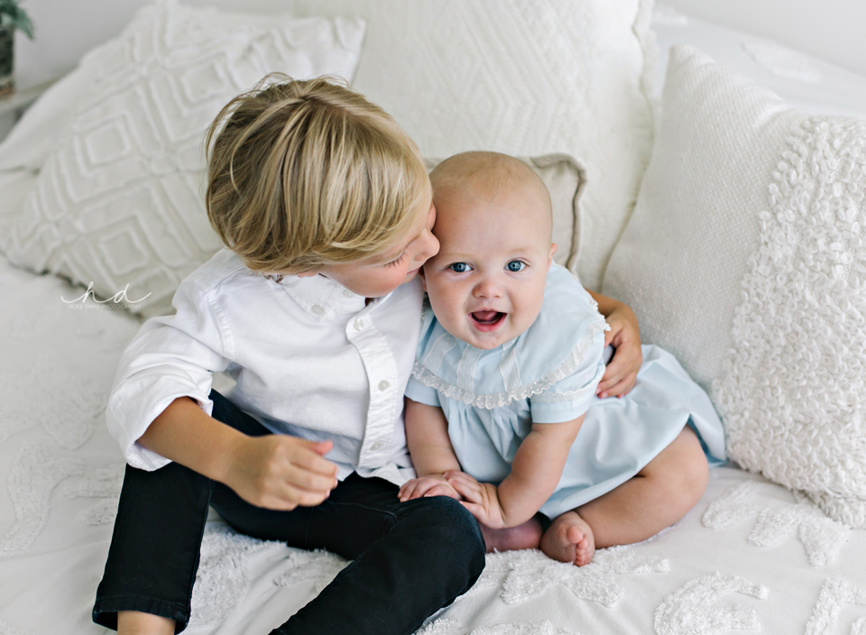Big brother kissing little brother sitting on bed Jackson area photography