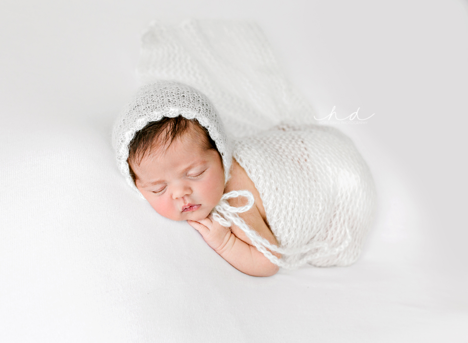 tushie up pose baby girl in white bonnet