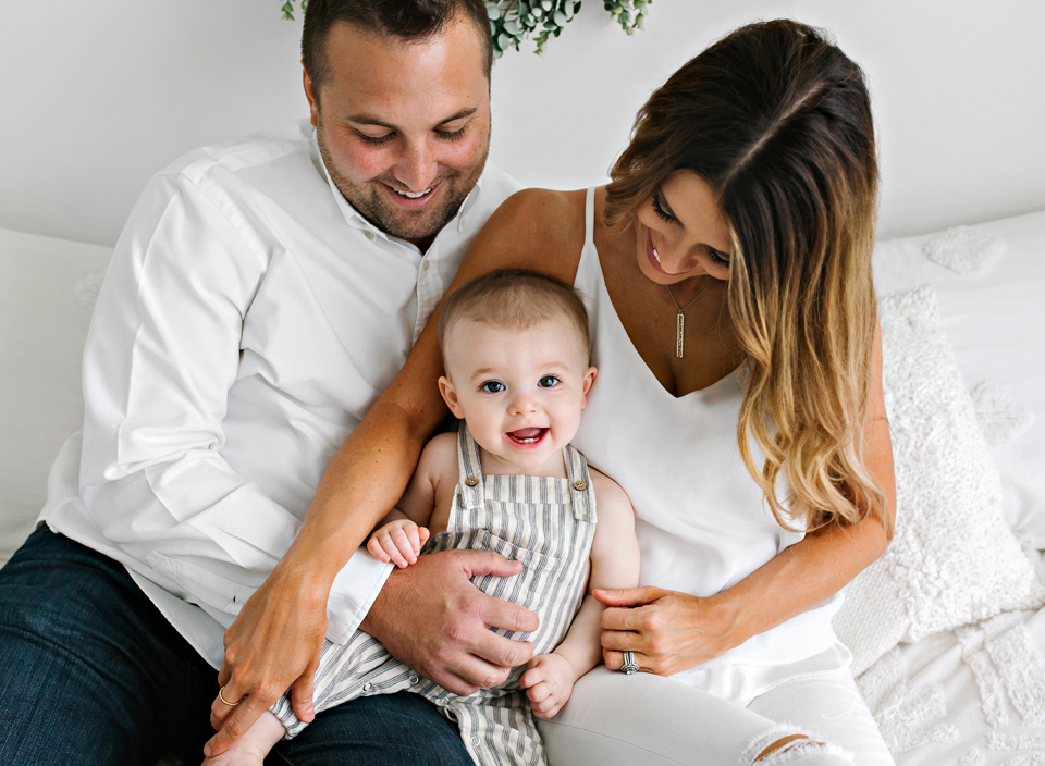 minimalist one year old family sitting on bed