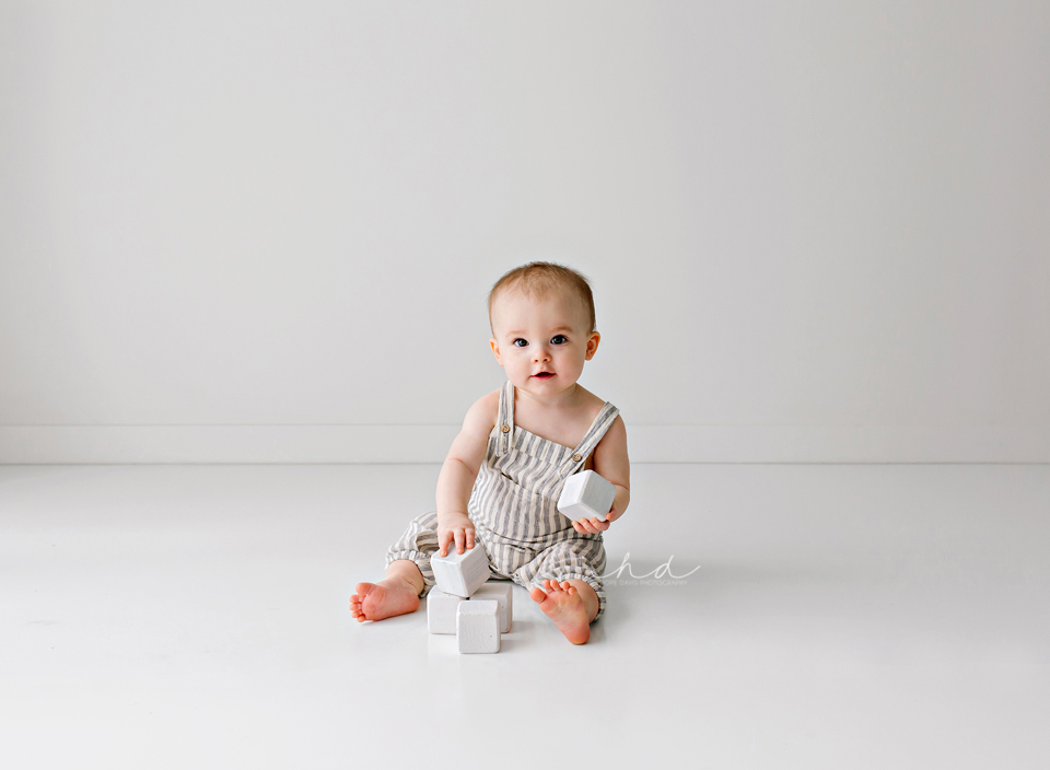 minimalist one year old photo shoot all white boy playing with blocks
