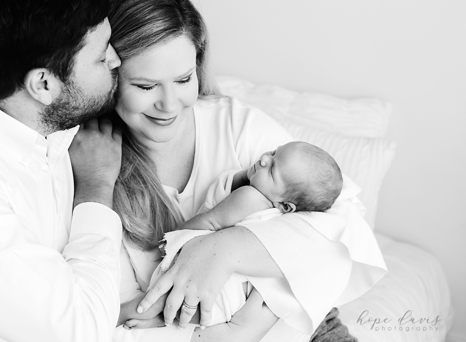 brandon ms best newborn photographer dad kissing mom while holding baby