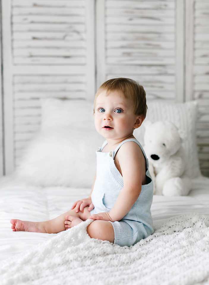 hope davis photography mississippi one year old sitting on white bed in blue overalls white studio