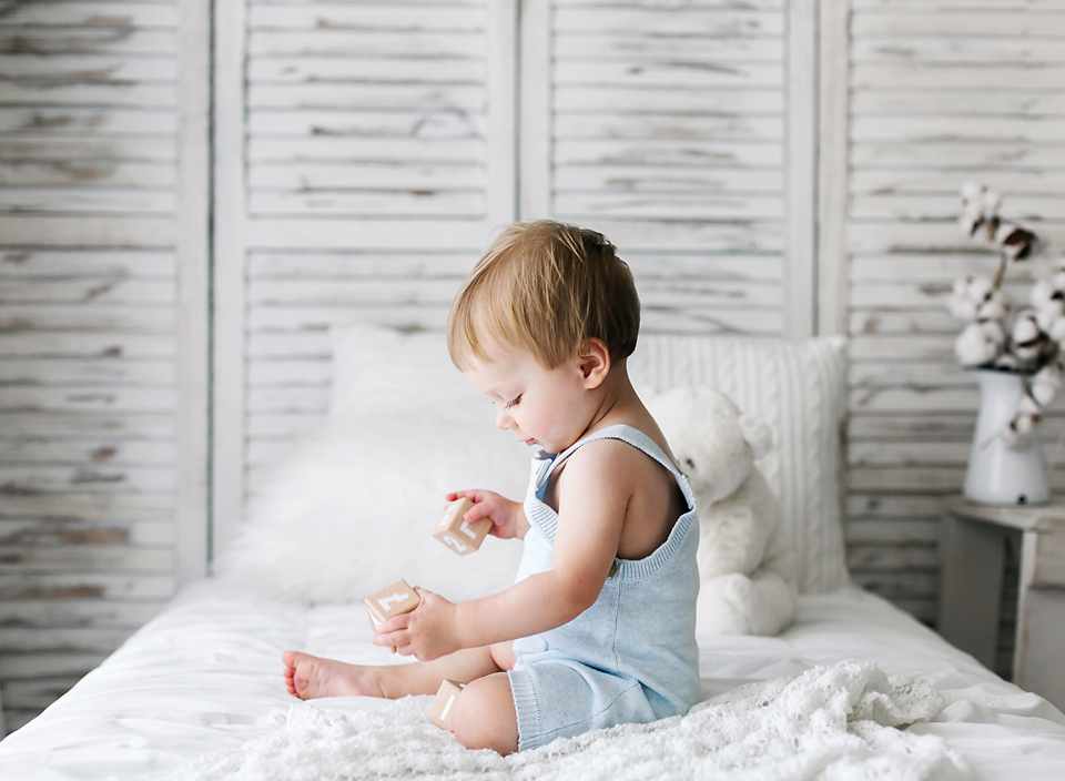 mississippi child photography little boy in blue overalls sitting on white bed playing with blocks hope davis photography