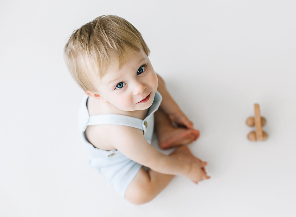 Baby boy sitting on floor in blue overalls playing with a wooden toy