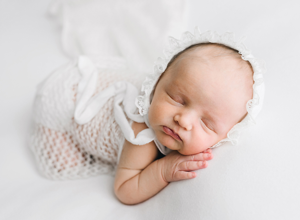 meridian ms baby photography newborn girl with bonnet laying on tummy