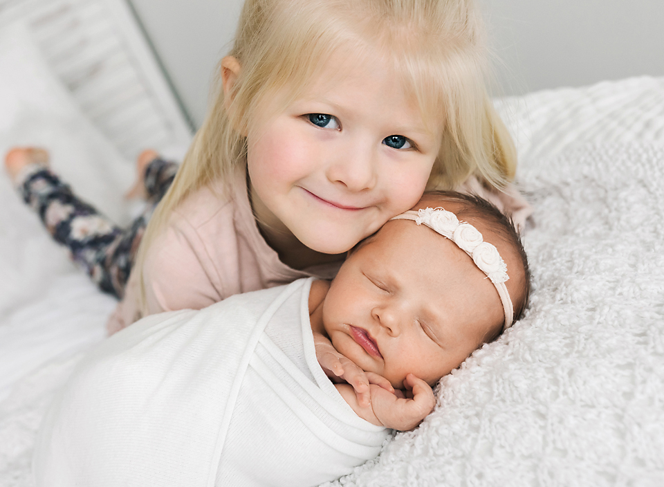 meridian ms family photographer newborn and sister on bed